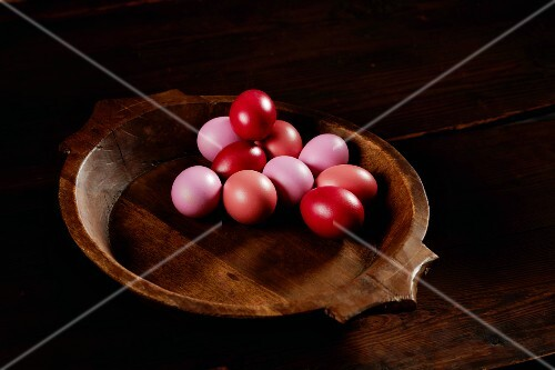 Pink and red Easter eggs in a wooden bowl
