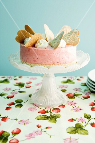 A strawberry ice cream cake decorated with wafers and cream