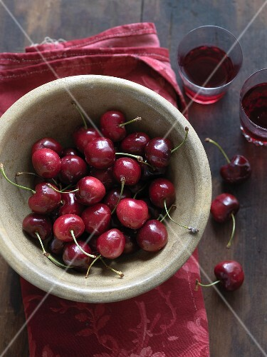 A bowl of fresh cherries and glasses of cherry juice
