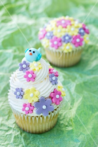 Lemon cupcakes decorated with sugar flowers and a bird