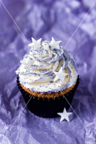 A cupcake topped with vanilla cream and decorated with stars