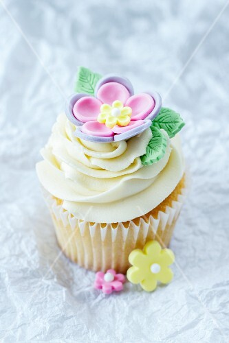 A cupcake topped with vanilla cream and decorated with a sugar flower