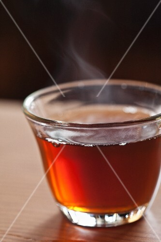 A glass cup of hot, steaming tea