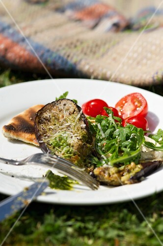 Grilled aubergine slices on pitta bread with rocket and tomatoes