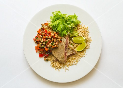 Tuna steaks served with a bean and tomato salad and rice