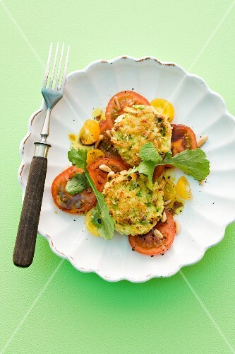 Asparagus cakes on a bed of tomato salad