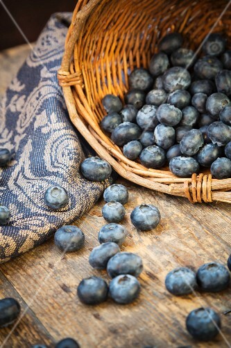 Blueberries in a basket and in front of it