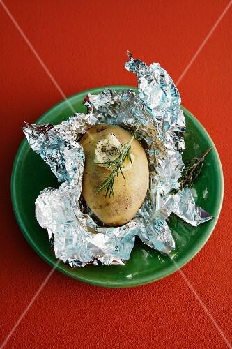 A baked potato with rosemary