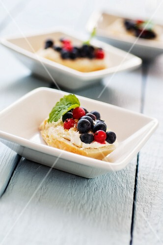 Slices of white bread topped with cream cheese and berries