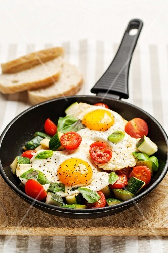 Fried eggs with courgettes and tomatoes