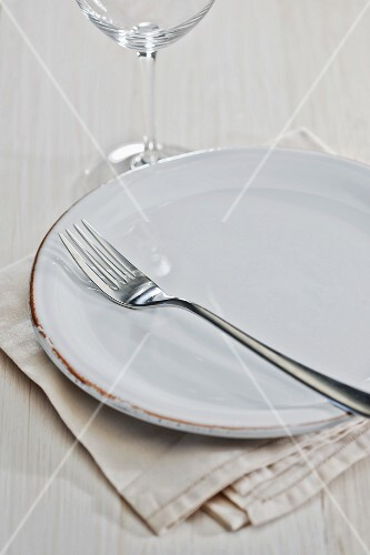A place setting with a plate, a fork, a wine glass and a napkin