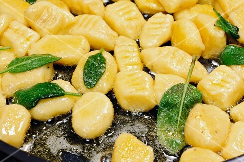 Gnocchi with butter and sage in a pan (close-up)