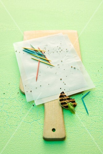 Breadcrumbs and toothpicks on a piece of paper