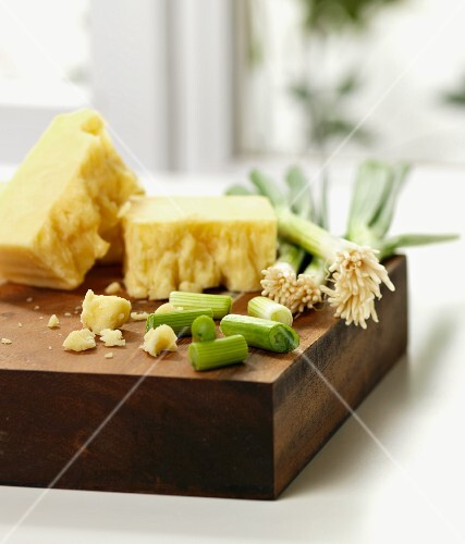 Cheese and spring onions on a chopping board