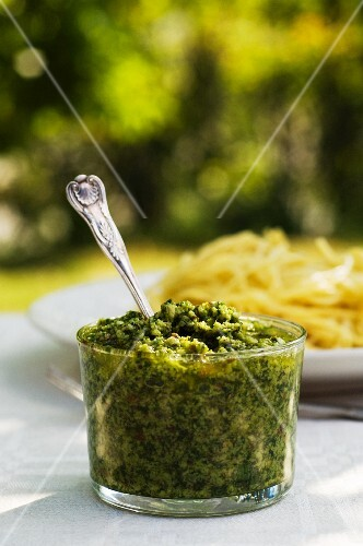 A jar of basil pesto on a garden table
