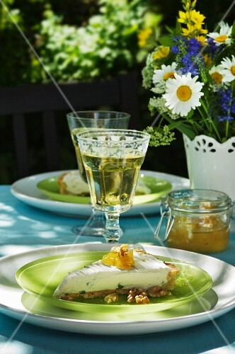 Slice of goat's cream cheese with walnuts and jam on a garden table