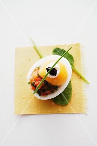 An egg with salmon tartar, crème fraîche and caviar