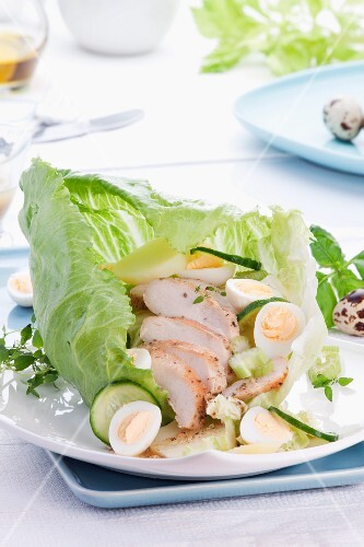 Chicken salad with quail's eggs and cucumber in a leaf lettuce