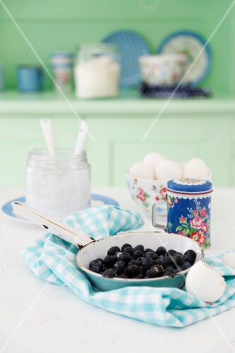 Blueberries in an enamel pan on a blue and white napkin with quark and eggs in the background