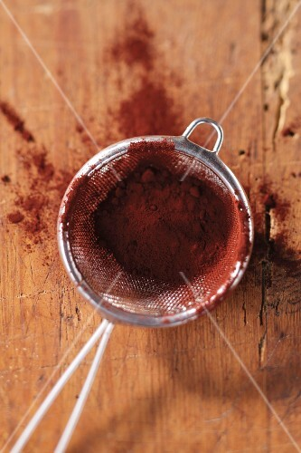 Cocoa powder in a sieve on wooden surface