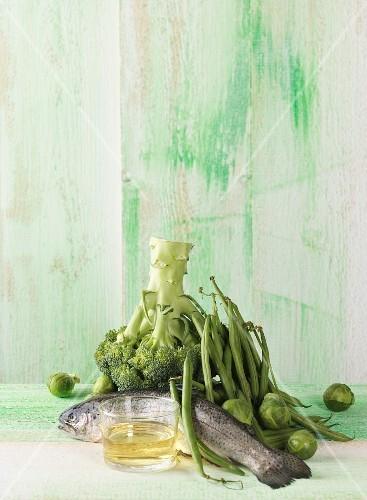 An arrangement featuring trout, green vegetables and oil (lipids)