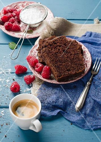 Chocolate cake with raspberries and icing sugar with a cup of coffee
