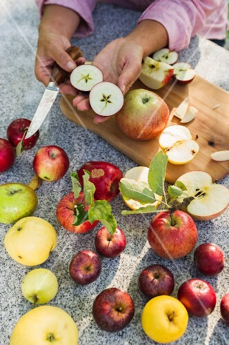 Various types of apples, whole and halved