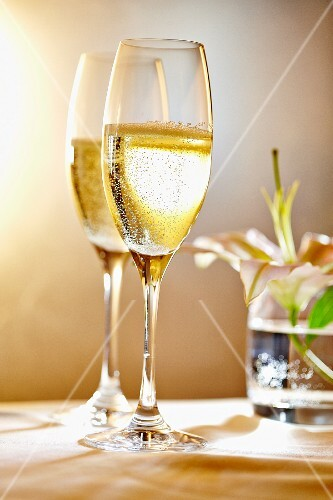 Two glasses of champagne in front of a vase of flowers