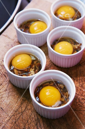 Oeuf Cocotte, raw eggs with mushrooms in oven-proof dishes ready to bake