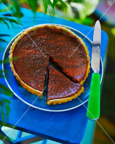 A caramel tart with a slice cut out