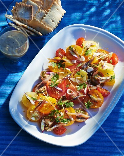 A salad made from red and yellow tomatoes with anchovies