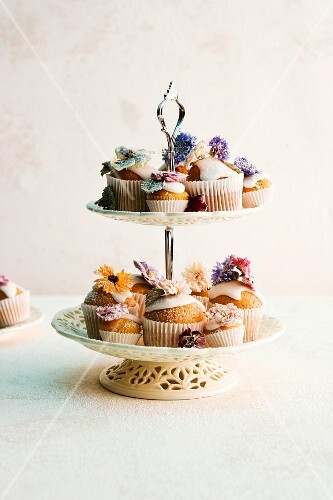 Various cupcakes decorated with flowers on a cake stand