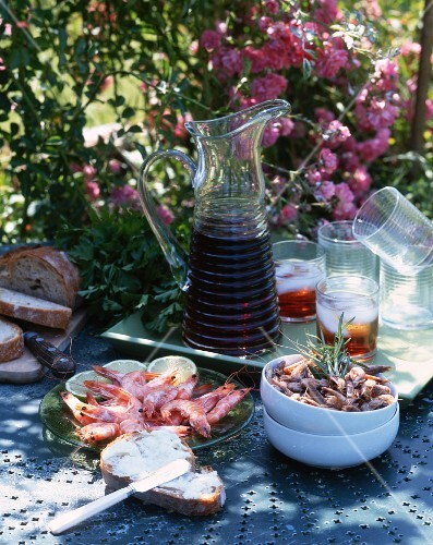 Seafood, bread and drinks on a table in a garden