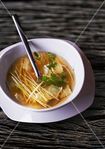 Broth with ravioli and vegetable strips