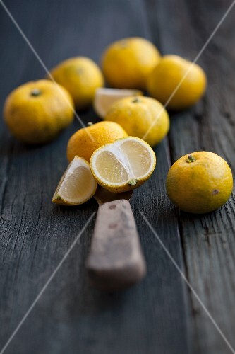 Yuzu fruits on a wooden surface with a knife