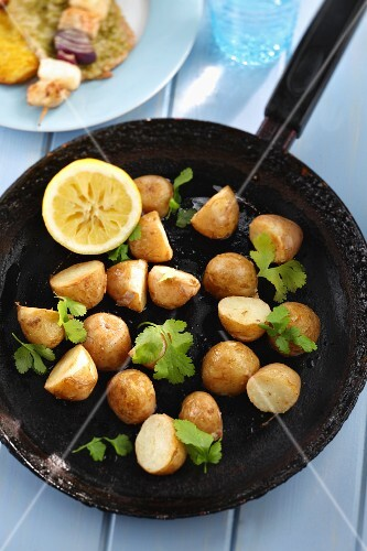 Fried potatoes with coriander in a pan