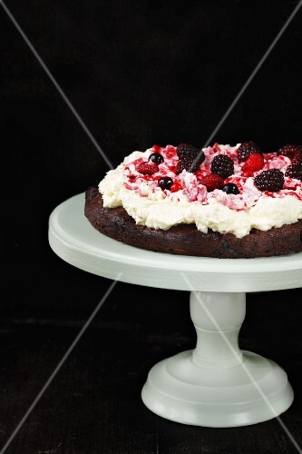 A chocolate cake topped with cream and blackberries