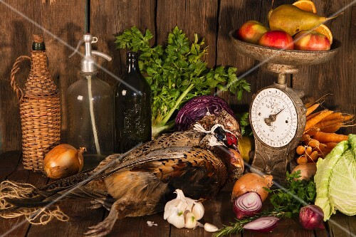 An autumnal arrangement featuring pheasant, vegetables, fruit, nuts and an old pair of kitchen scales