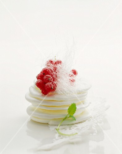 Meringues topped with redcurrants and sugar threads