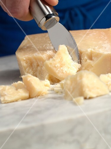 Pieces of Parmesan being broken off with a cheese knife