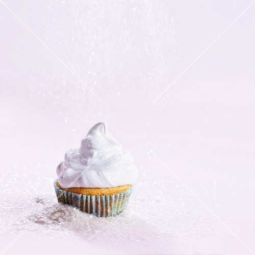 A cupcake topped with cream and sprinkle with sugar