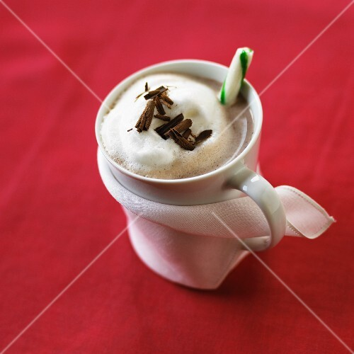 A mug of hot chocolate with milk foamy, grated chocolate and a candy cane