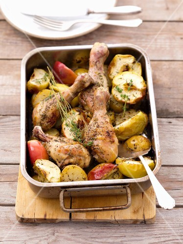 Roast chicken legs with apples in a roasting tin