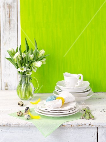 White crockery with Easter decorations and a bunch of spring flowers