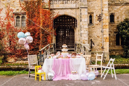 A wedding cake on a festively laid table in front of a church