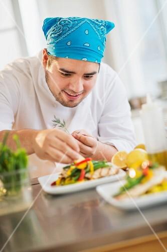A chef garnishing a dish