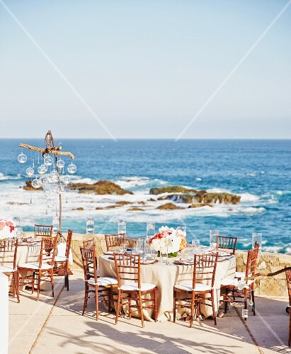 Tables laid on the terrace of a beachside restaurant for a wedding reception