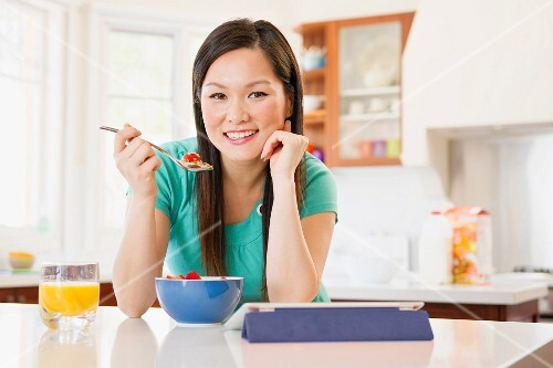 A Chinese woman eating muesli in kitchen