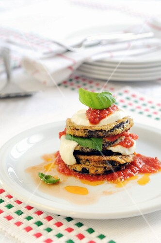 A stack of fried aubergine slices, tomatoes and mozzarella with tomato sauce and basil