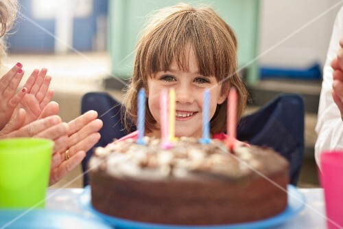 A little girl sitting behind a large birthday cake